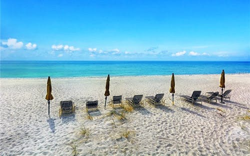 A line of chairs and umbrellas on the beach